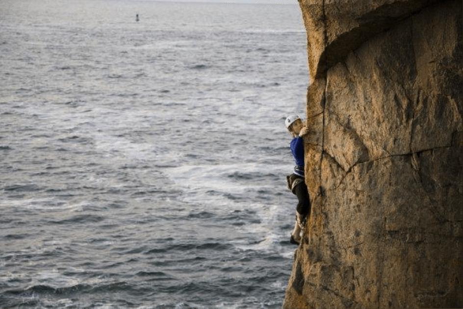 Katy DeGrass rock climbing next to the ocean